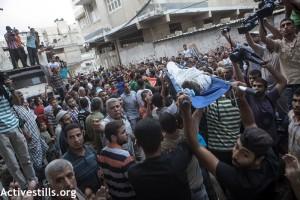 Le corps d'un des enfants de la famille Shuheibar est porté lors des funérailles de Afnan (8) Jehad (10) et Wassim (9) dans le quartier de Tuffah, à la ville de Gaza, le 17 Juillet 2014. Trois enfants de la famille Shuheibar: Afnan , et ses cousins- Jehad et Wassim, ont été tué le même jour par un missile tiré d'un drône israélien, alors qu'ils jouaient sur le toit de la maison familiale.
